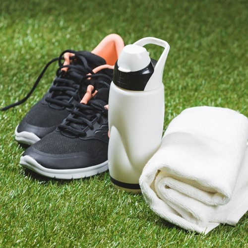 trainers, water bottle and towel on an outdoor pitch